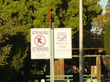 Foto von einem Schild am Bahngleis: Active Railroad - No Trespassing; There is help: 1.800 Suicide