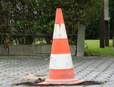Photo of our court entrace with a filled pothole and a pylon standing on it.